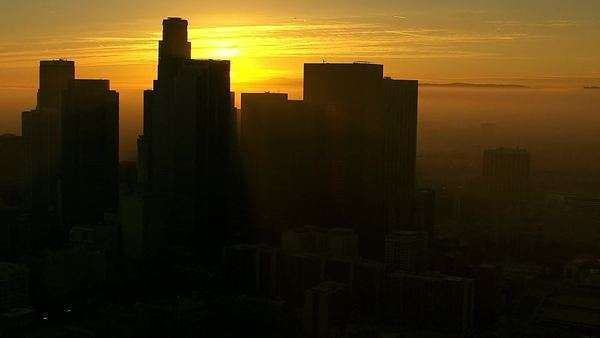 Aerial view of silhouetted Los Angeles skyscrapers at sunrise Royalty-free stock video