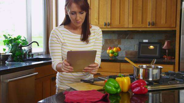 Woman with digital tablet in kitchen cooking Royalty-free stock video