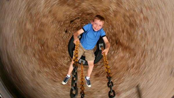 Young boy spinning tire swing at school playground Royalty-free stock video