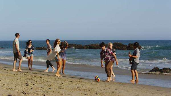Group of young people walking together along beach Royalty-free stock video
