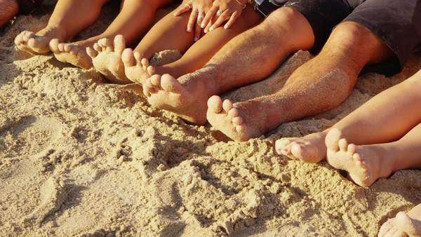Group of young people with feet in sand, closeup Royalty-free stock video