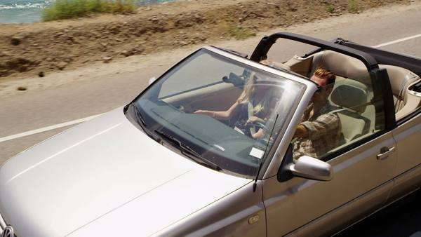 Couple driving convertible together along beach Royalty-free stock video