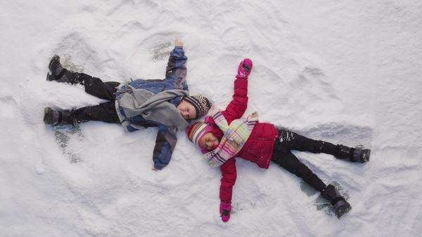 Two kids in winter making snow angels Royalty-free stock video