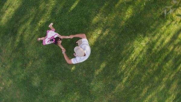 Overhead shot of father spinning around with daughter in yard Royalty-free stock video