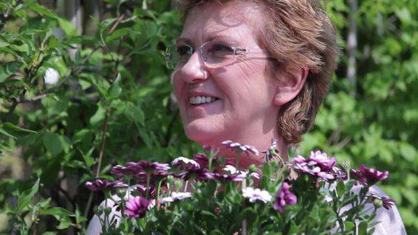 Portrait of mature female with flowers in garden centre Royalty-free stock video