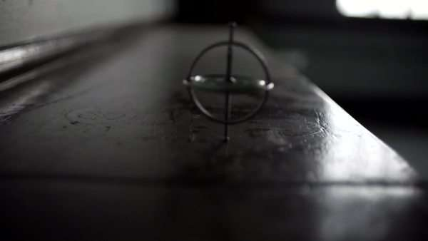 An antique top spins on a dusty, dark wooden table Royalty-free stock video