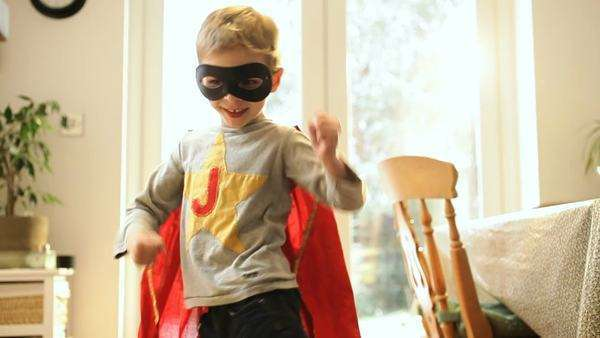Boy wearing cape and pretending to be superhero at home / London, Greater London, United Kingdom. Royalty-free stock video