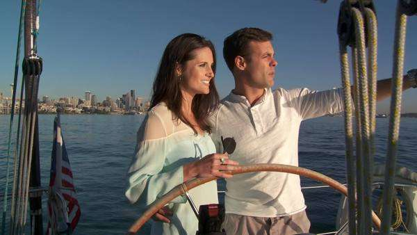 Young couple takes the helm of a sailboat with the city skyline behind them  Filmed on the Puget Sound in Seattle, Washington, with sunset approaching Royalty-free stock video