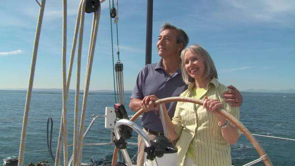 Happy mature couple taking the helm of a yacht on the Puget Sound in Seattle, Washington  Couple holds hands as they sail Royalty-free stock video