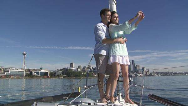 Young couple take pictures of themselves and the city skyline as they stand at the front of a sail boat on the Puget Sound in Seattle, Washington  Wide shot Royalty-free stock video