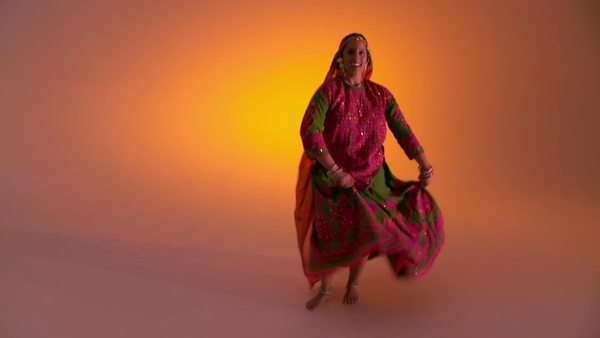 Indian woman in traditional folk costume swirls her skirts as she dances against an orange colored background  Full length shot Royalty-free stock video