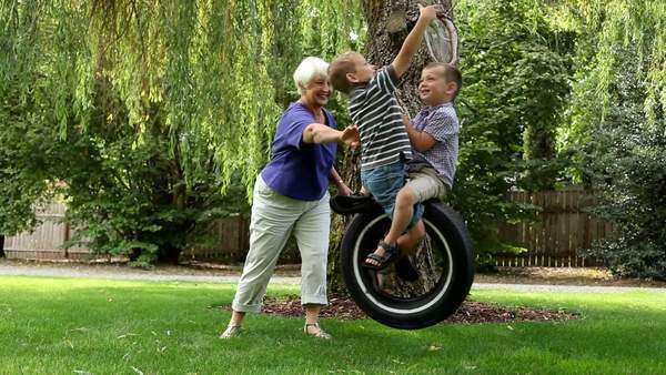 Woman pushing grandchildren on swing Royalty-free stock video