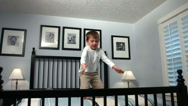 Young boy jumps on bed, slow motion Royalty-free stock video