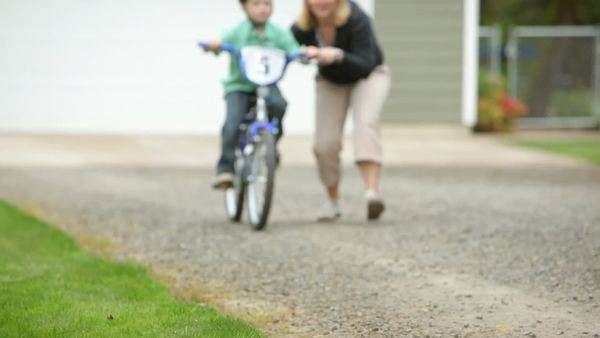 Mom helping son ride bicycle Royalty-free stock video