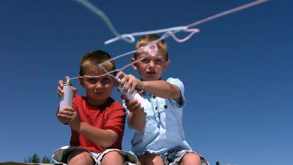 Two young boys shoot silly string, slow motion Royalty-free stock video