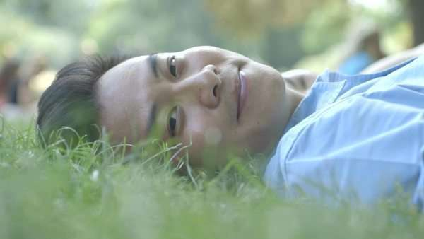 Young man relaxing on grass in park Royalty-free stock video