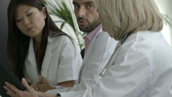 Doctors consult a tablet while meeting in a boardroom Royalty-free stock video