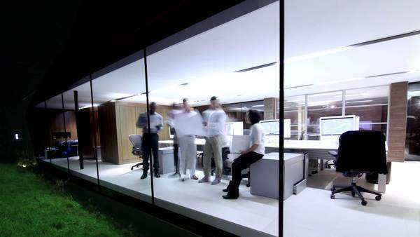 Staff working late into the evening in contemporary architects' offices, timelapse Royalty-free stock video