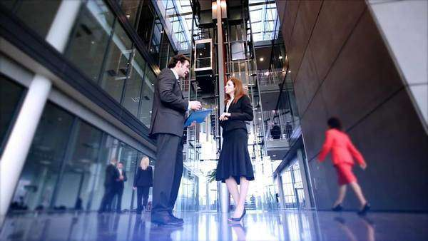 Businessman and woman talking, low angle Royalty-free stock video