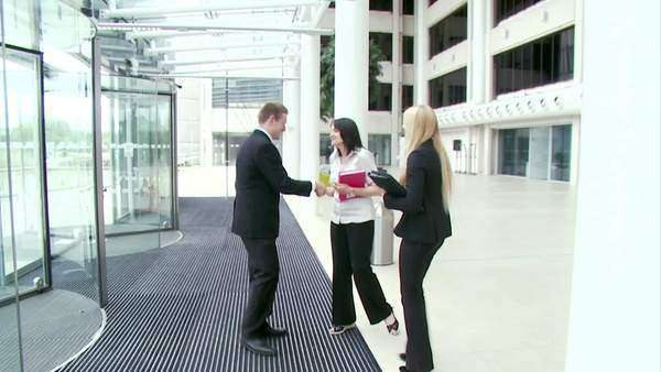 Businesswomen greeting businessman in the office lobby Royalty-free stock video