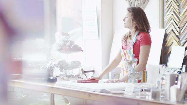 A bored female shopkeeper with no customers takes off her apron and looks wistfully out of the window. In slow motion. Royalty-free stock video