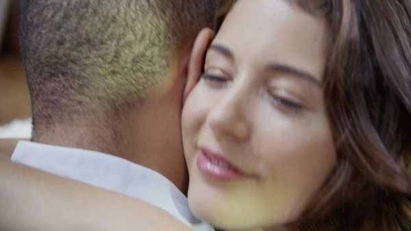 Extreme close up of a young happy couple holding each other in a loving, lingering embrace. In slow motion. Royalty-free stock video