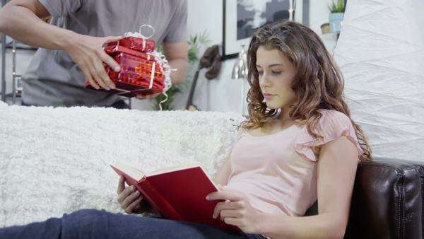 Attractive young woman is surprised by her partner who gives her gifts while she's reading and relaxing at home. In slow motion. Royalty-free stock video