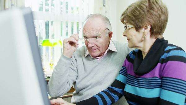 An elderly couple are browsing the internet together and looking to book a holiday online Royalty-free stock video