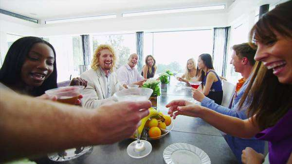 Happy group of friends at a cocktail party raise their glasses for a toast. In slow motion. Royalty-free stock video