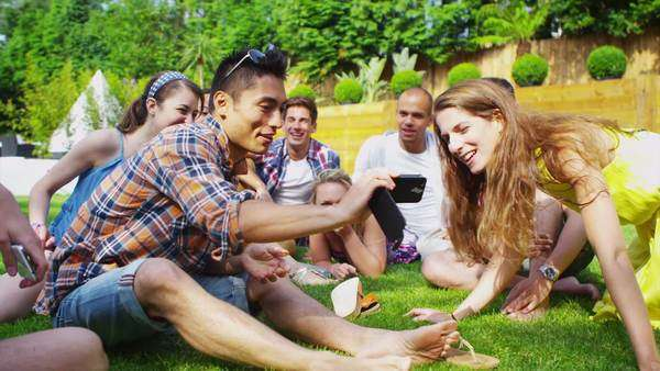 Cheerful group of young friends relaxing outdoors together on a summer day and taking photos with a camera phone. In slow motion. Royalty-free stock video