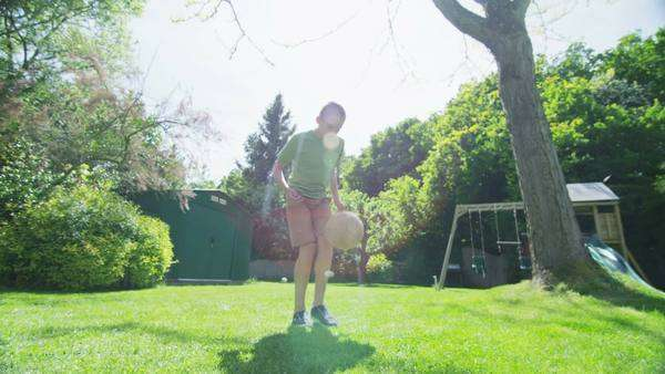 Active young boy practising his soccer skills in the garden on a bright sunny day. In slow motion. Royalty-free stock video