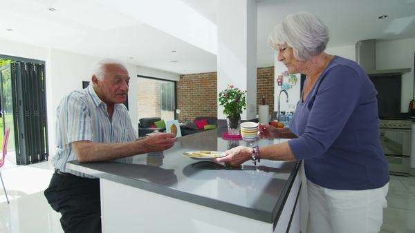 Happy senior couple enjoy cookies and hot drinks, as they relax together in the kitchen of their modern home. In slow motion. Royalty-free stock video