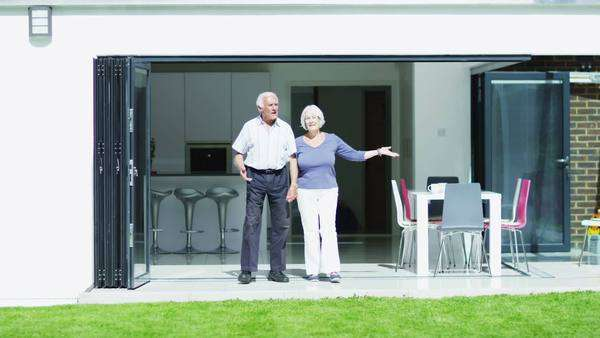 Romantic senior couple in modern home show they are still young at heart as they dance together in the doorway, overlooking their garden. In slow motion. Royalty-free stock video