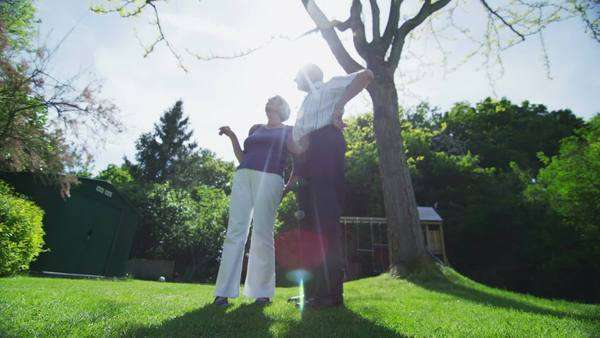Romantic retired couple embrace as they look out over their garden on a summer day. In slow motion. Royalty-free stock video