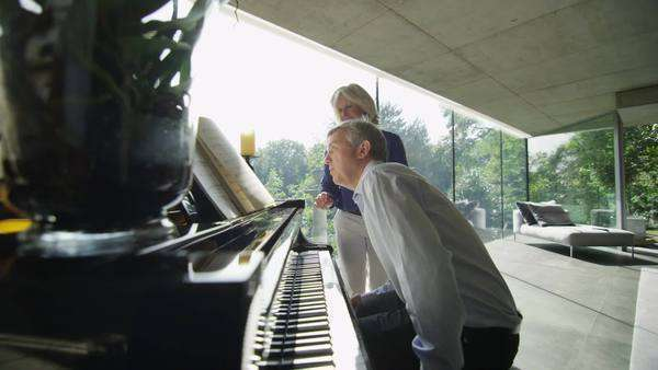 Mature man plays the piano in contemporary home as his partner listens Royalty-free stock video