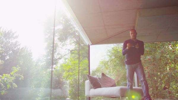 Attractive man in modern glass home takes a look at the view outside Royalty-free stock video