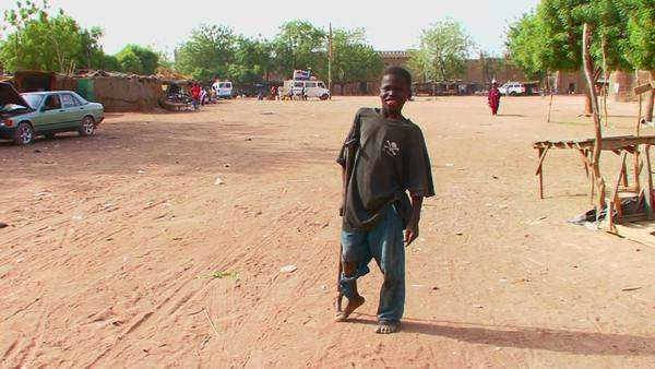 A boy walks on crutches in a poor African town. Royalty-free stock video
