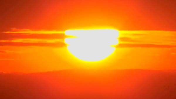 The sun slowly sets through the clouds in a huge orange ball. Royalty-free stock video