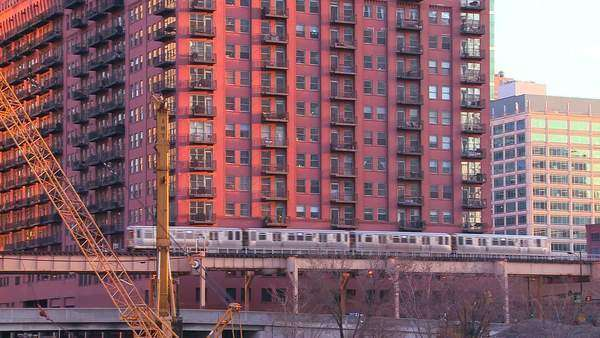 The El train travels over a bridge in front of the Chicago skyline and apartments. Royalty-free stock video