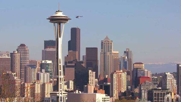 Beautiful establishing shot of Seattle Washington on a sunny day with a helicopter flying by. Royalty-free stock video