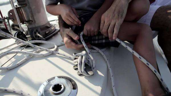 Father and son holding rope on yacht, close up Royalty-free stock video