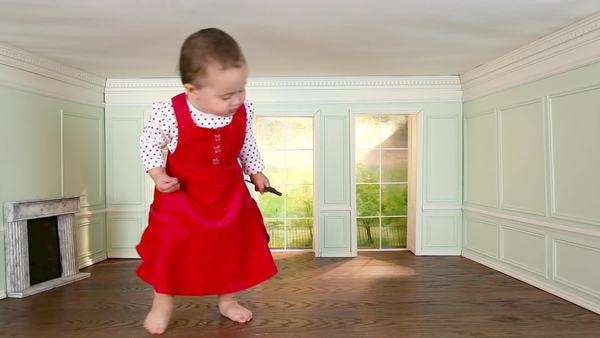 Giant toddler girl walking around in tiny room with key Royalty-free stock video