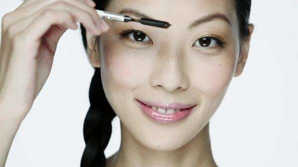 Young woman using eyebrow comb Royalty-free stock video
