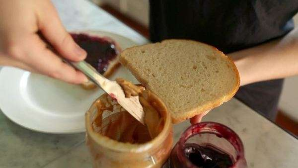 Close up of child making peanut butter and jelly sandwich Royalty-free stock video