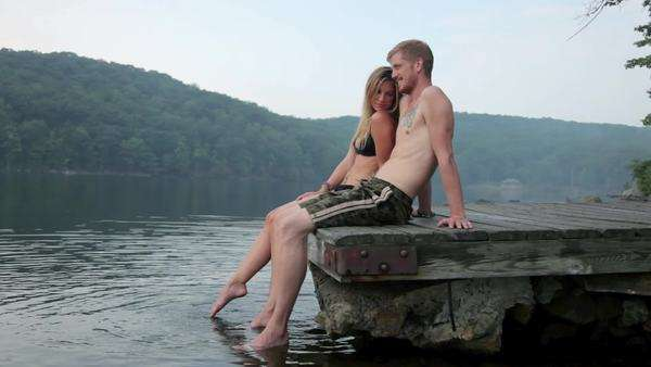 Couple relaxing together on pier at lake Royalty-free stock video