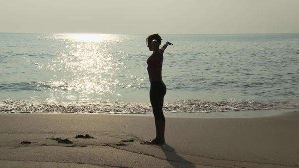 Woman performing sequence of yoga poses by the ocean Royalty-free stock video