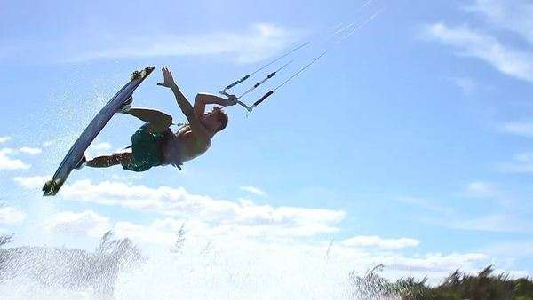 Young man does kite surf trick over camera Royalty-free stock video