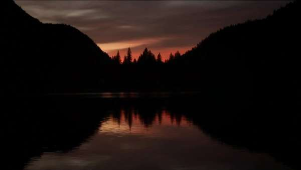 Sunset and mountains mirrored in a still lake Royalty-free stock video