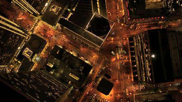 Aerial vertical view at night of city traffic illuminated by city streets and skyscrapers, North America, USA Royalty-free stock video