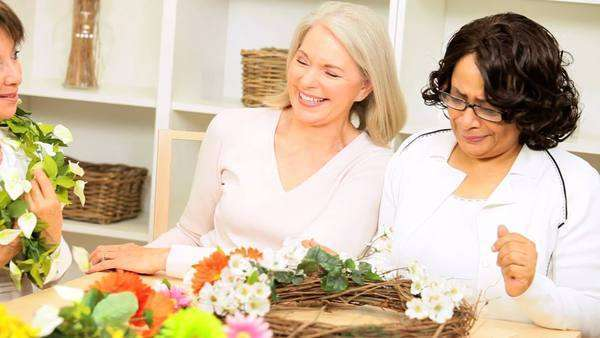 Laughing senior ladies having fun with artificial flowers while crafting at home Royalty-free stock video